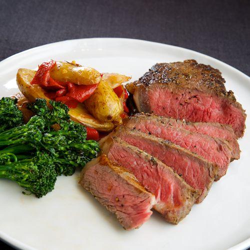 bistec a la parilla | new york strip, fingerling potatoes, piquillo peppers, pearl onions, rapini, pasilla demi glace