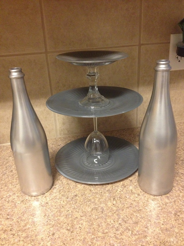 Cake stand: Get $1 store glass plates, candlestick holder, wine glass, gray primer spray paint & metallic matte aluminum paint. Prime the back of plates let dry then metallic paint over primer. Let dry then glue together.  Candlestick holders: wine/sparking cider bottles and same paint as above. Clean bottles and take of labels. Prime let dry then paint metallic over primer.