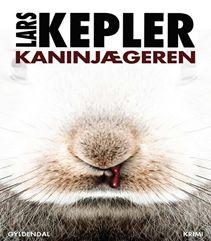 """Kaninjægeren af Lars Kepler (Bind 6): Kriminalkommissær Joona Linna har siddet to år i et sikret fængsel, men transporteret væk til et hemmeligt møde med politiet, som har akut brug for hans hjælp for morderen benævnt som """"Kaninjægeren"""" er på spil. Klik på fotoet og læs mere."""
