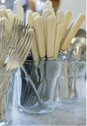 Cream bone handled cutlery in tumblers. We had those knives when I was growing up.