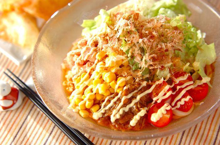 野菜たっぷりのヘルシーな簡単サラダうどん。レタス、プチトマト、ツナ、水煮コーン、瓶入りナメタケをのせ、麺つゆとマヨネーズをかけてかつお節をのせる、ボリューミーな一皿!