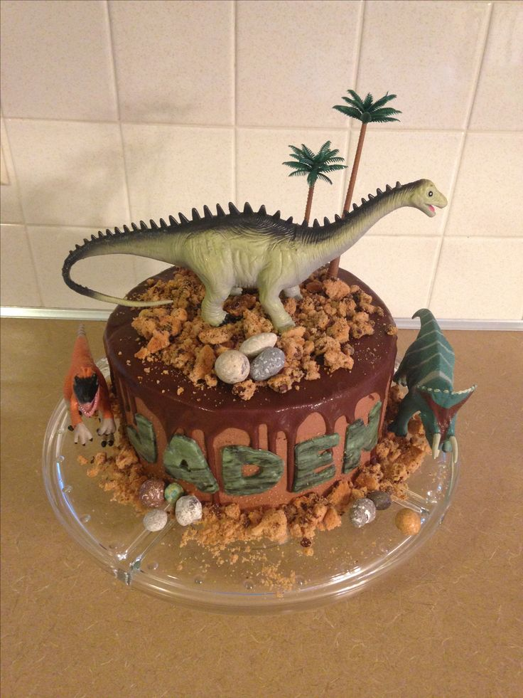 Easy dinosaur birthday cake with crumbled chips ahoy, chocolate rocks and chocolate ganache. Dinos purchased at Hobby Lobby, trees at Michaels.