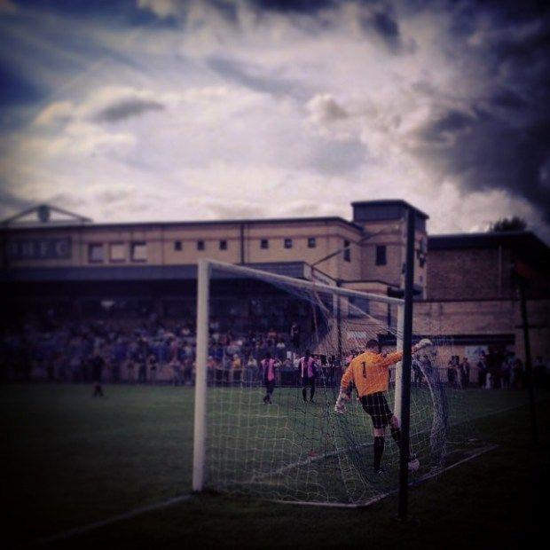 The Harrow Borough goalkeeper retrieves Dulwich Hamlet's winning goal from the back of the net
