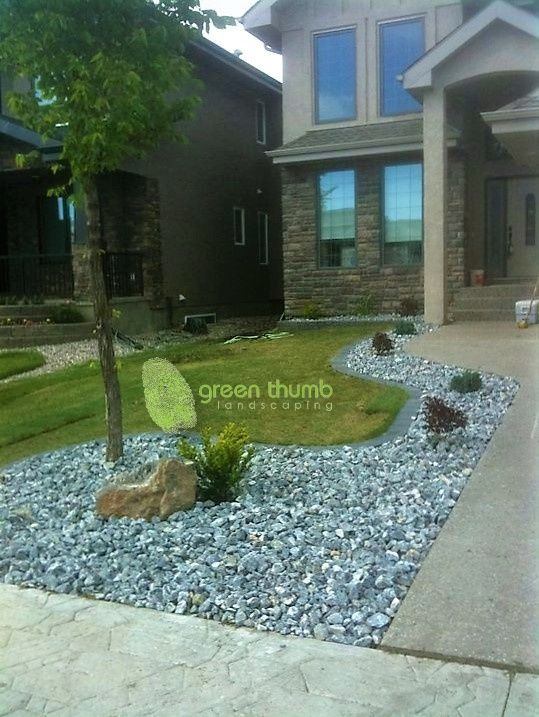 40mm Rustic crushed rock bed with cobblestone edging and a small accent boulder. The edging provides a clean edge that eliminates the need for trimming.