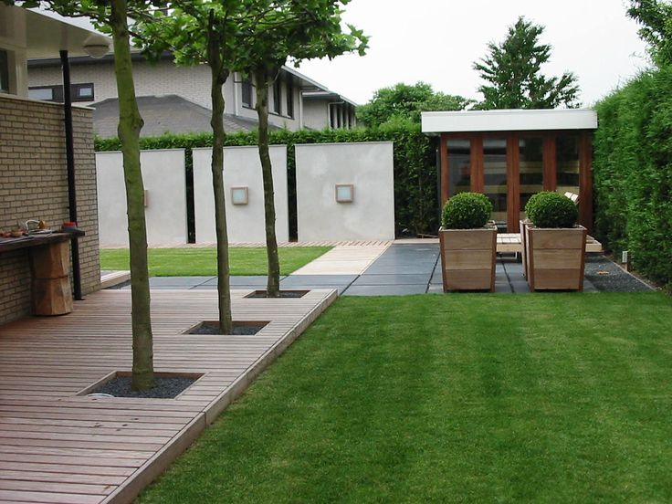 The grass looks very healthy and the garage with the white wall are very nice. Combined with the small trees it gives the garden a restful appearance.