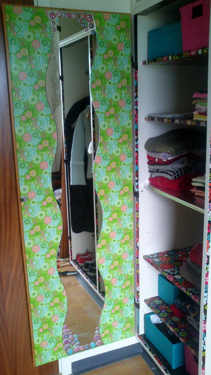 Gift wrapping paper on the inside of the wardrobe-door. On top of that is a frameless mirror glued tight.