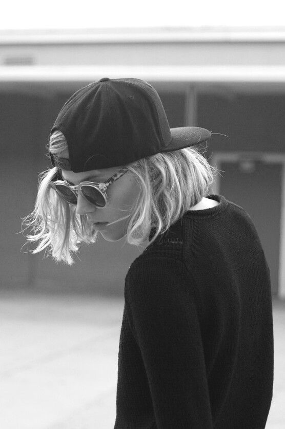 Tomboy with blond bob, cap and shades.