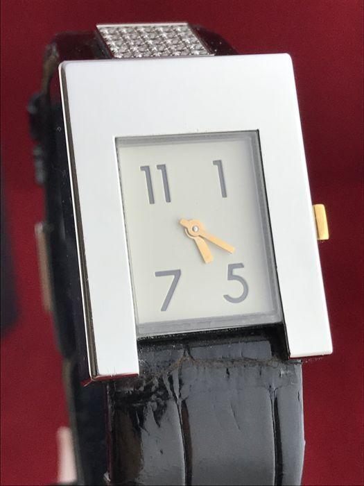 """POMELLATO """"Stress"""" vrouwen polshorloge - goud en diamanten - NOS  Beschrijving:POMELLATO """"Stress"""" - vrouwen polshorloge. Staal met zwarte glanzende lederarmband en gesp sluiting. Witte wijzerplaat met Arabische cijfers en gele gouden handen - geel gouden push-down kroon. Het horloge heeft de unieke eigenschap van de toevoeging van een elegante plein-vormige plaat verfraaid met witte diamanten. Een uurwerk maar ook een item van juwelen.Materiaal:Geel goud - staalEdelstenen:Witte…"""