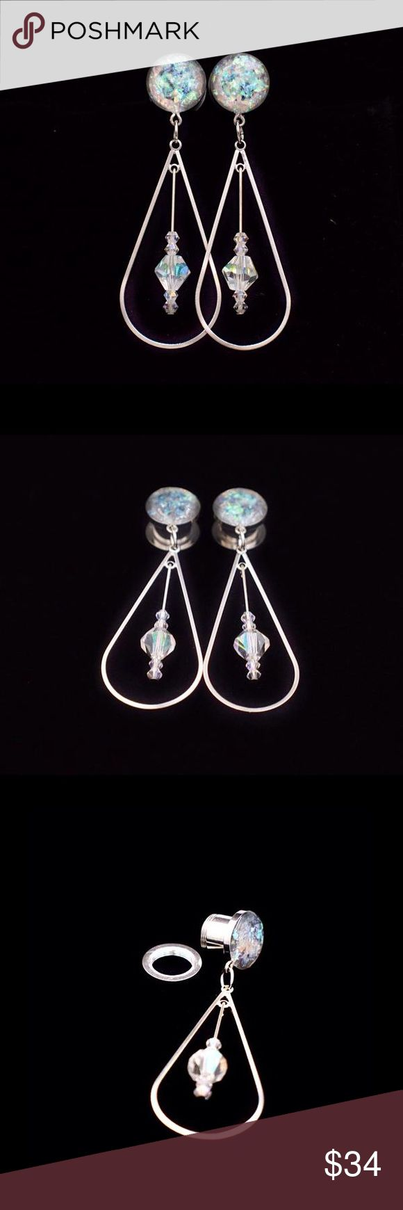 Holographic Crystal Teardrop Dangle Plugs Orders are Made & Shipped in 1-2 business days A pair of absolutely gorgeous Holographic Crystal Teardrop Dangle plugs. These start with a beautiful holographic top that features a silver teardrop dangle with crystal gems. The teardrop piece hangs down about 1 1/2 inches and is about 1 inches wide. The plug is a high grade 316L surgical steel with a screw on backing that makes them easy to put in and no having to worry about them falling out. Jew