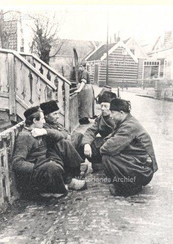 Haven. Vooraan Jan Sul 'Sulletje', visser 1876-1937. Naast hem Kees van Dirk de Boer, visser 1869-1925, die op 4 september 1925 plotseling overleed terwijl hij aan het roer van de botter stond. Op de achtergrond staat Huibertje Bond (Huip van Ouwe Hein) toe te kijken (1878-1957). Verder in het mannengroepje zien we nog Thames Plat, Alias `Thames Vet', vrijgezel en Kees Bien, vissersknecht 1872-1953, getrouwd met Agie van de Koolsnijer. ca 1920 #NoordHolland #Volendam