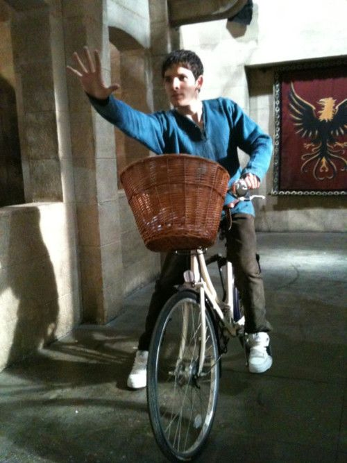 """In an medieval castle, wearing part of his costume, Nikes, riding a bicycle, and using magic."" Because Colin Morgan, like a boss."