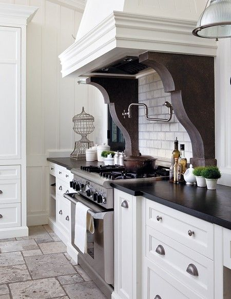Modern conveniences, like the wall-mounted spigot tap over the stove for filling pots, update the country-style kitchen in this home. Massive stone corbels support the range hood, adding interest and a sense of history to the new-build house.
