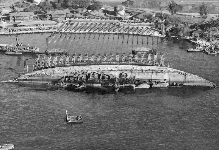 Battleship USS Oklahoma (BB-37), sunk at Pearl Harbor on 7 December 1941, is re-floated. This is an aerial view of the salvaged Oklahoma toward shore in 90 degree position, March 19, 1943.
