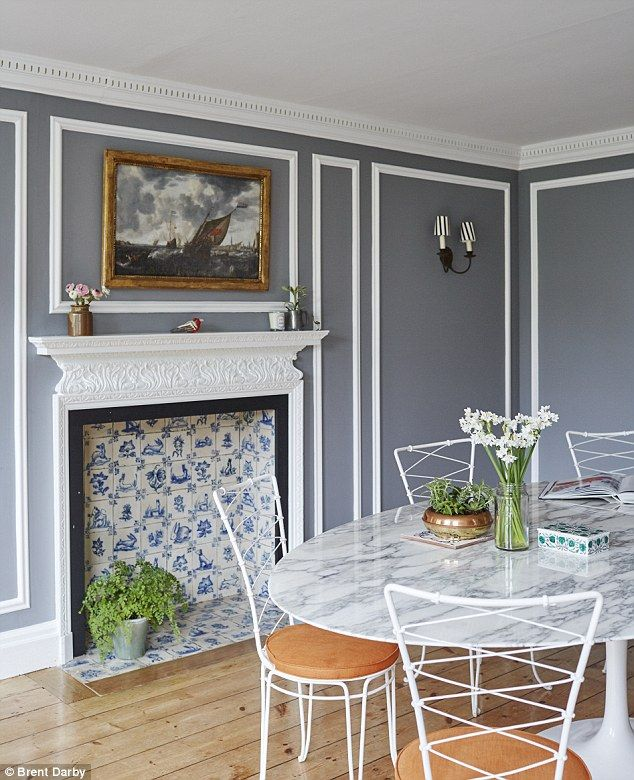 The fireplace takes centre stage in the dining room. 'The previous owners had plastered over most of it,' explains Celia. 'It was an amazing find.' Above hangs a 17th-century Dutch painting. The walls are painted in Farrow & Ball Lamp Room Gray (farrow-ball.com) with the panelling details highlighted in Dulux Trade white (dulux.co.uk). The classic Eames Tulip marble-top table is teamed with vintage 1950s garden chairs bought in France