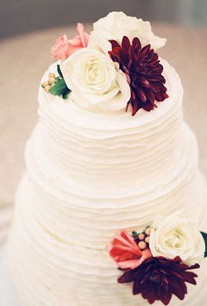 A buttercream wedding cake with marsala and cream colored flowers for a fall wedding.