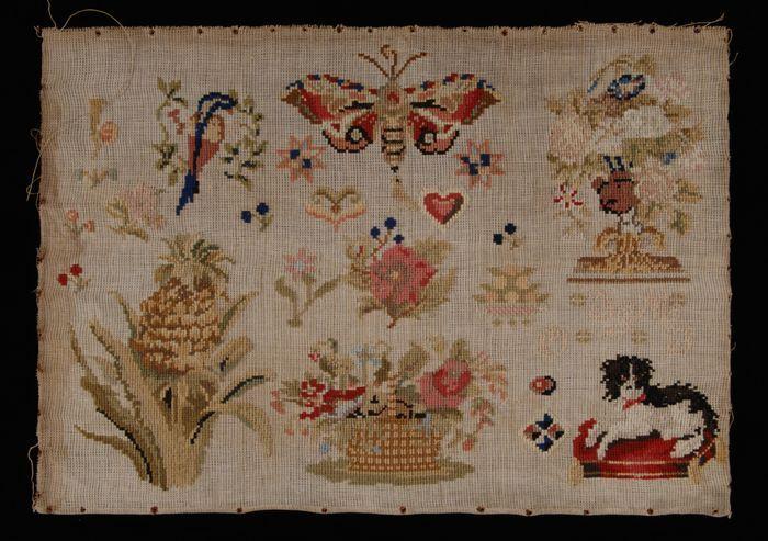 """Merklap gewerkt in kruissteek in veelkleurige wol op grof wit katoenen stramien in mattingbinding, gemerkt """"IeM / 11 / O / I"""""""