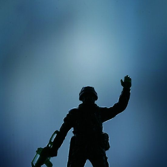 Toy soldier carrying machine gun waving on plain blue background. Color digital artistic photograph by Edward Olive commercial portrait photographer from Madrid Spain.