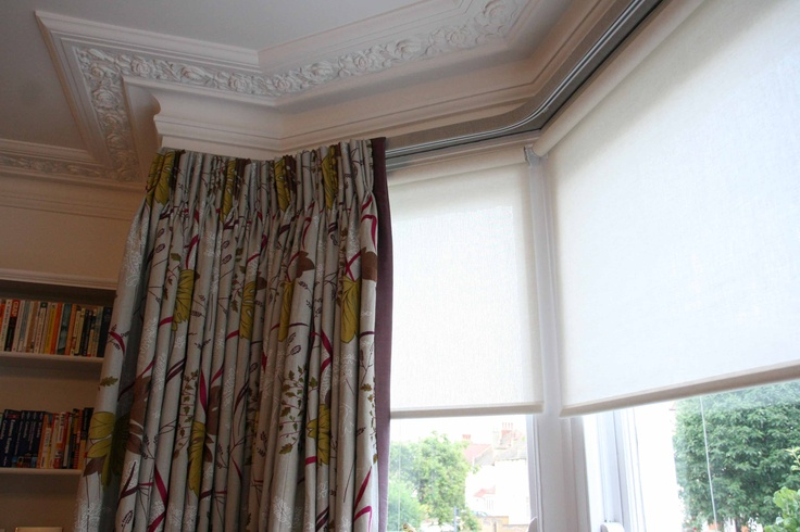 Bay window: sprung loaded roller blinds sit neatly behind the curtains on the underside of the lath and fascia, and provide privacy from the road, plus valuable protection from the sun's rays for the embroidered linen curtains and their aubergine coloured silk border