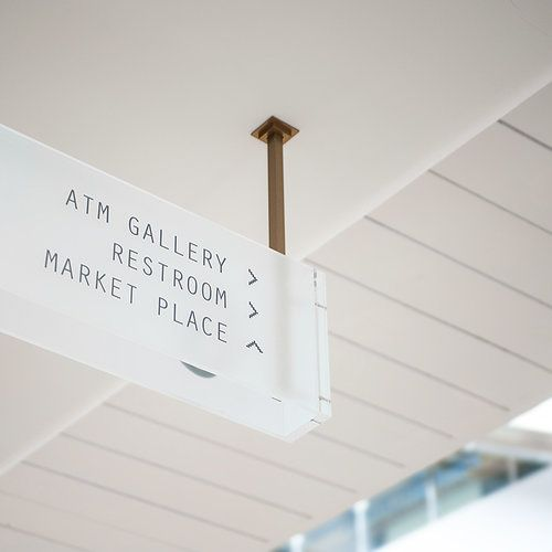 Overhead directional signage in frosted glass, with copper coloured metal frames.