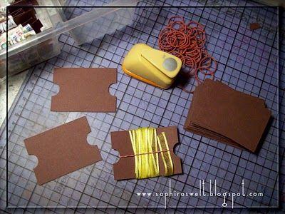 Cartes de rangement pour rubans faites avec du carton (s'il est trop mince, la carte se pliera). Elles sont de format A7 (soit un A4 coupé en deux par deux fois). Les deux petits côtés sont perforés d'un demi-cercle afin d'y glissé l'élastique qui maintiendra les rubans en place.