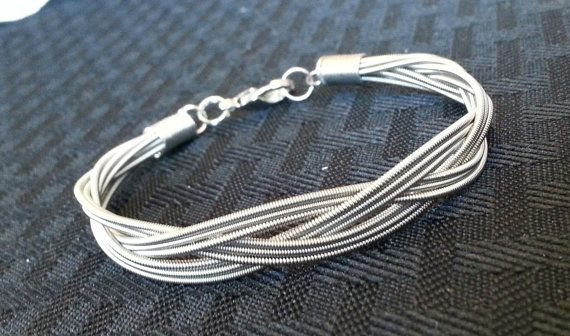 This bracelet is made by braiding 9 recycled guitar strings in a 3-string braid pattern, and attaching them using a lobster clasp. It measures 7 3/4, but it can be sized if you wish. Just be sure to send me a message with your desired size.