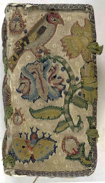 Front cover of an embroidered satin book  with remnants of a pair of satin ties.  The New Testament of our Lord and Saviour Jesus Christ. [and] The Whole Booke of Davids Psalmes.   (London, 1640)