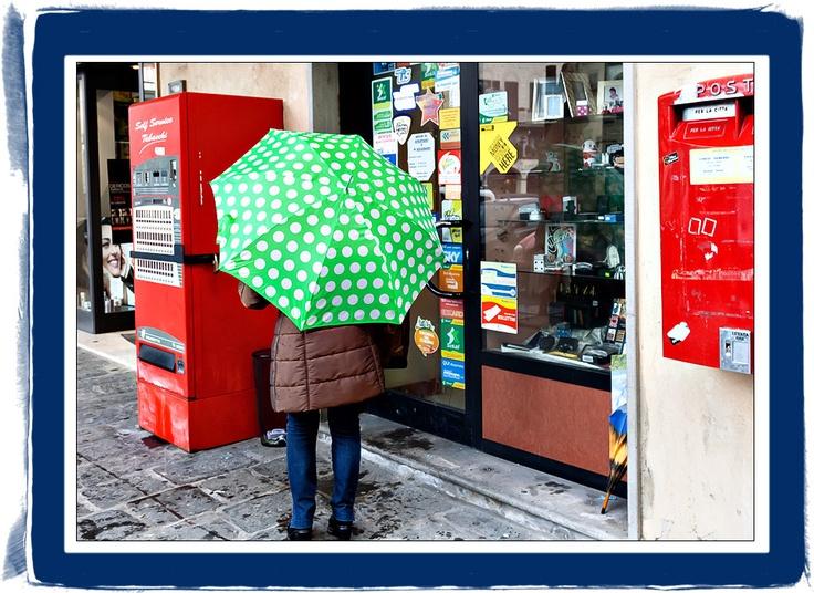 Una donna con ombrello verde e pantaloni blu davanti al tabaccaio
