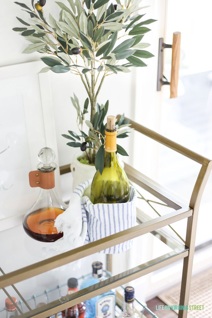 Bar cart styling with glass and leather decanter, olive tree, white wine, blue and white striped towel. Part of A Summer Lemon Tablescape blog post.