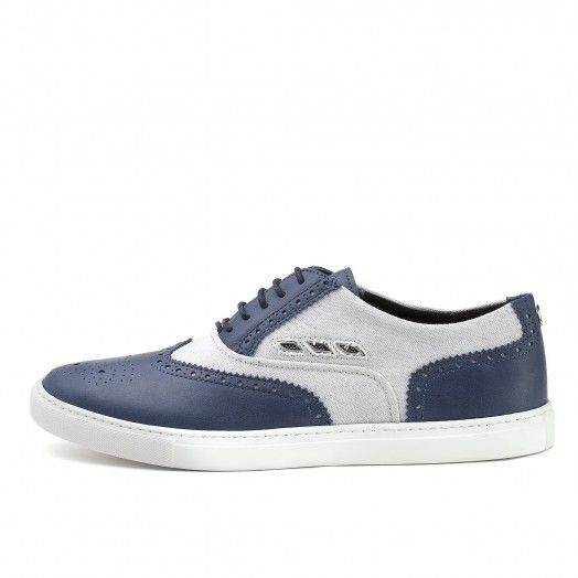 The men's Maserati New England shoe is an Oxford-style sneaker, elegant but at the same time informal, characterised by a grey cotton upper with soft blue leather inserts. There are various Maserati branding details on the upper, such as the three side ai