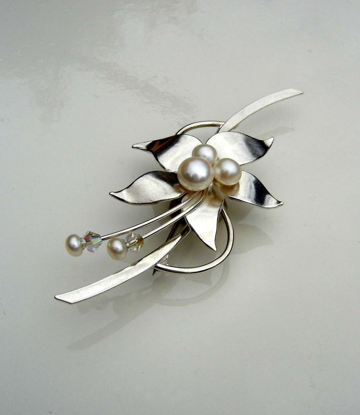 Adorned by Sally Silver floral brooch: A brooch made in sterling silver and set with freshwater pearls and crystal beads
