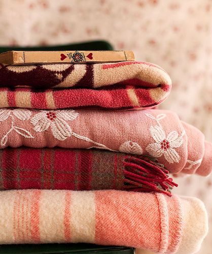 Warm wool blankets in shades of red and pink