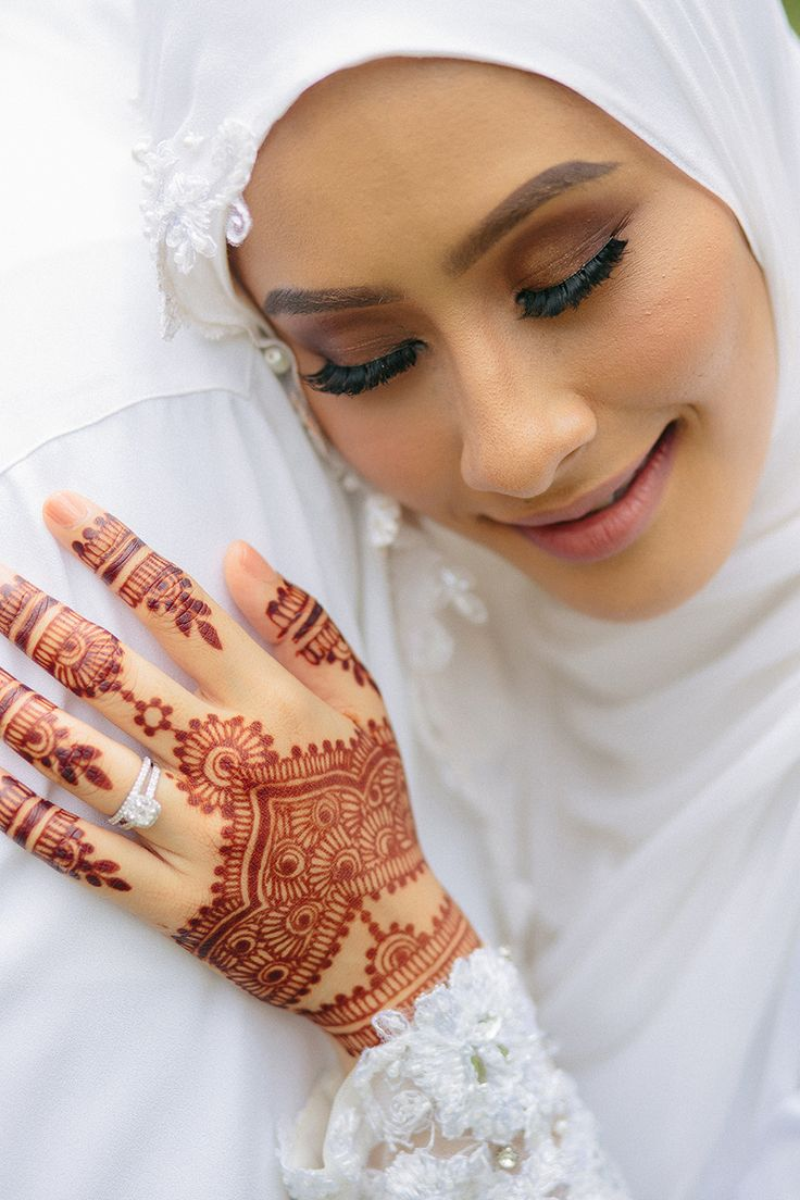 Bride in traditional Malay wedding costume and henna tattoo with gorgeous sparkling engagement ring with a natural make-up look and soft colours // Razif and Sarah decided to celebrate their Singapore wedding solemnisation, or nikah, at Ba'alwie Mosque in a meaningful and intimate ceremony captured by Zakaria Zainal of We Made These. The couple looked resplendent in all white against the immaculate dais decorated by Fleursdeco