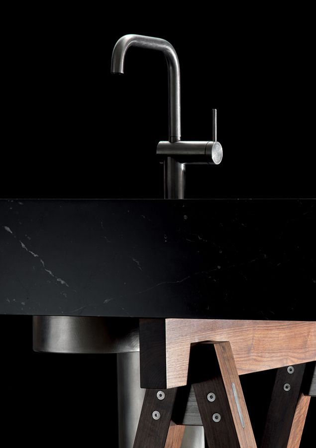 LANDO | Dolmen Kitchen, Convivio, design by Enzo Berti | Matt Marquinia Black marble top, walnut stands and shelves, hand-brushed stainless steel details | Made entirely of marble, the Dolmen kitchen top presents a sculptural and monolithic appearance in the matt Marquinia black, Calacatta Borghini White and Carrara white versions. In this unique stone form, the functions of cooking and washing, spaced out with broad worktops, have been skillfully integrated.