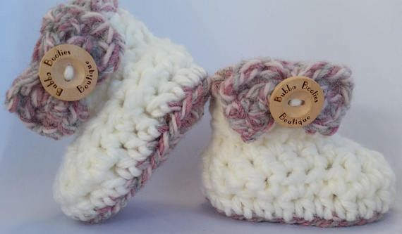 Handcrafted pink and white baby booties with bow and