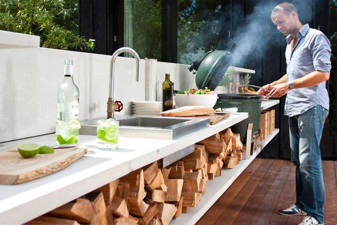 Outdoor kitchen designed and adapted for outside cooking, using wood and a big green egg, rather than trying to create outside versions of inside appliances.