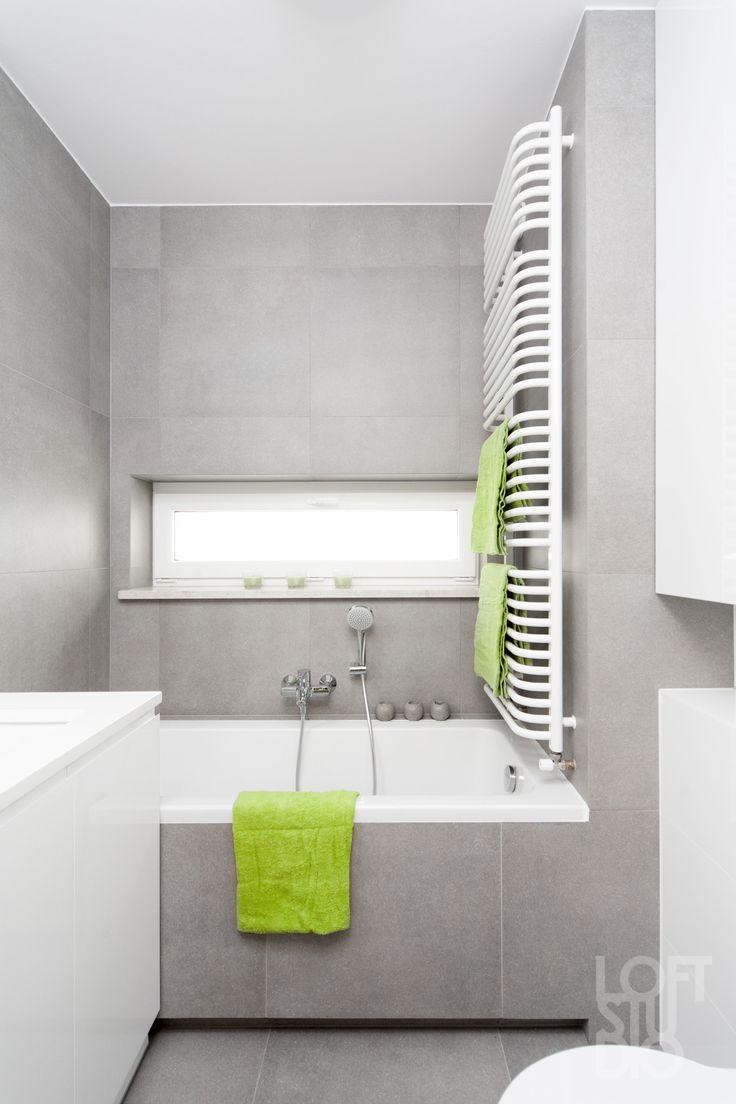 white heater in apartment design by LOFTSTUDIO/ biały grzejnik na tle szarych płytek w projekcie LOFTSTUDIO Pragniesz podobnego wnętrza to zgłoś się do nas www.loftstudio.pl
