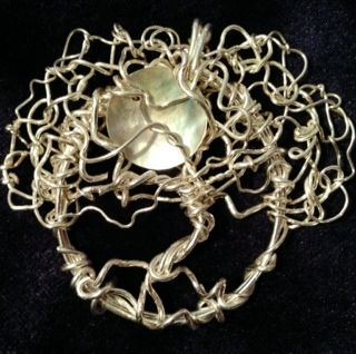This is a Winter Tree of Life pendant by Dot Wasilewski It is made with silver wire and has a Mother of Pearl Moon Come see more of these lovely pendants at our show on Dec 14 th at Bronson Centre