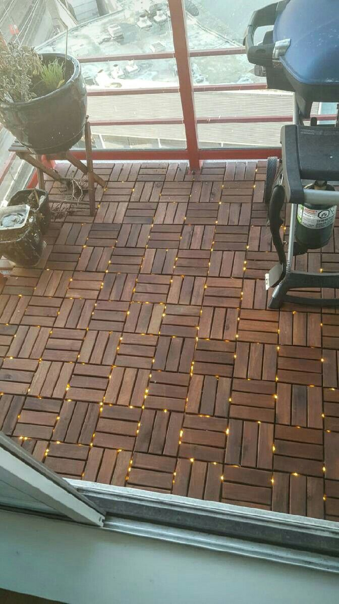 Ikea deck tile with fairy lights between tiles, upgrading a Vancouver condo balcony.