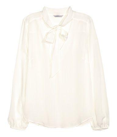 Hvit. En langermet bluse i lett, vevd viskosekvalitet. Blusen har ledig passform og er v-ringet med knytebånd i halsringnigen. Lett avrundet nederst.