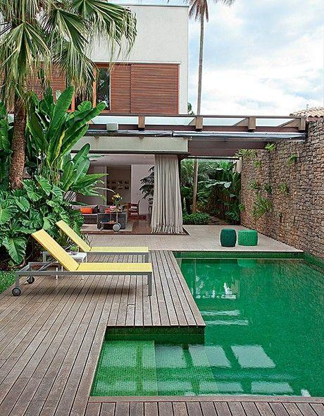Na reforma do Estúdio Cada Um, a casa foi aberta para o jardim, com deque, piscina de pastilhas verdes e plantas tropicais. O muro de pedras com espécies nos vãos é outra atração do projeto
