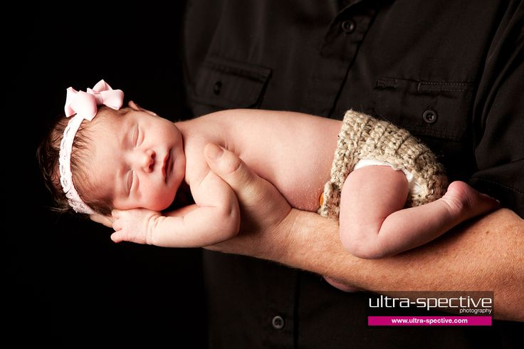 Newborn girl with bow on dads arms forever my baby by ultra spective photography a modern photography studio in livermore ca