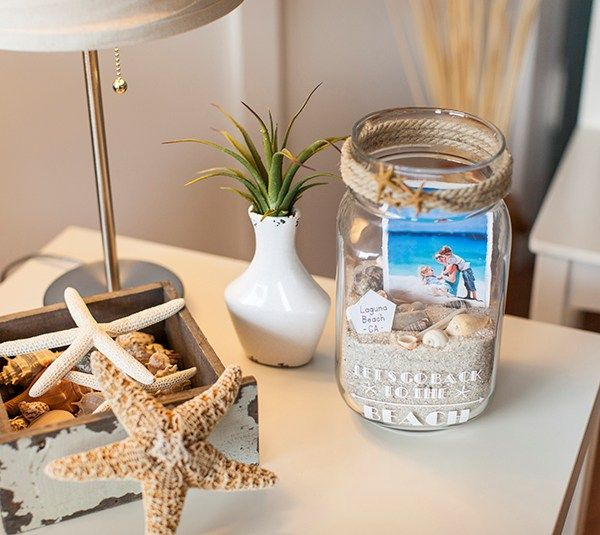 """Beach Memory Jar  I love the beach so much. You may have heard me say that before! I get there and I never want to leave. Sadly, I have to. So, this time I decided to bring a small container of sand home with me. I used it in this photo memory jar which is a beautiful way to showcase photos of our trip.  My jar is 9"""" tall and 17 ½"""" around. Images are from the Cricut® Life is a Beach digital cartridge and the Cricut® Art Deco and Cricut® Simple Celebrations digital fonts.  ❤ Shanon  DIY"""