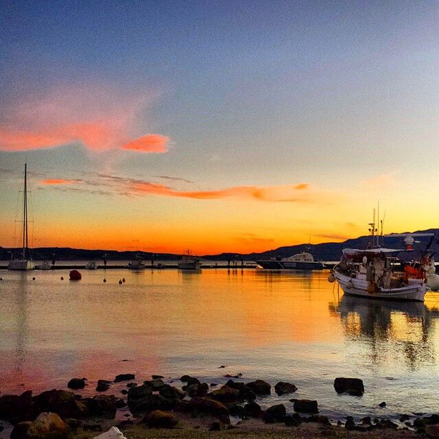 The port of Milos island (Μήλος) , called Adamantas . Magical colors of the sky mirroring at the sea , sunset time ⛅️.