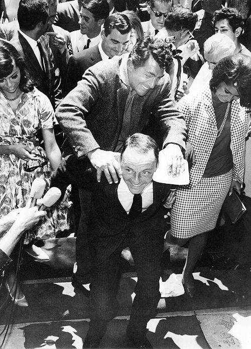 Nancy Sinatra, Dean Martin, and Tina Sinatra help Frank place his footprints in the cement at Grauman's Chinese Theater on July 20th, 1965.