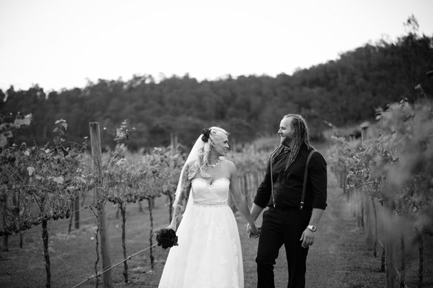 black and white image of newlyweds holding hands as the smile at each other