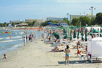 MAMAIA, ROMANIA - AUGUST 5: Tourists enjoy on crowded beach on Aug 05, 2011 in Mamaia, Romania. Mamaia is Romania's oldest, largest and best resort at Black Sea Coast.