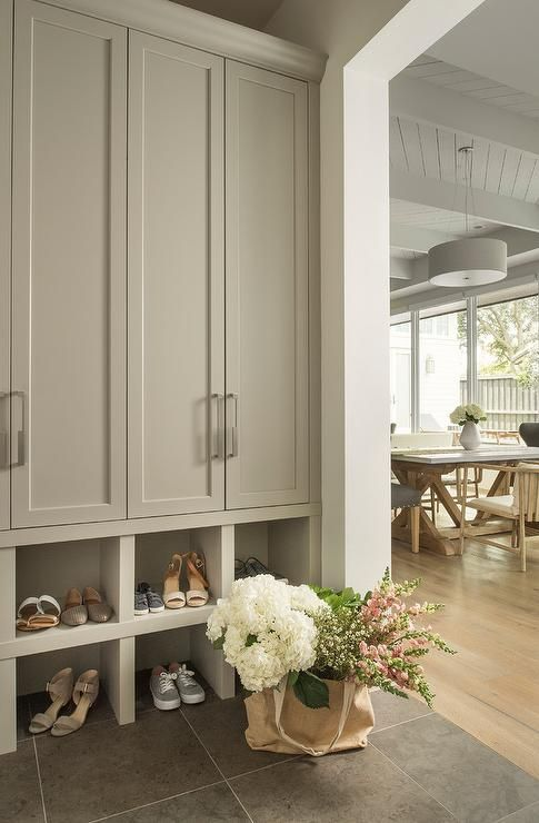 Gray mudroom features tall light gray closed lockers with nickel pulls fixed above stacked light gray shoe shelves fixed against slate floor tiles.