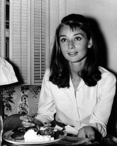 Audrey Hepburn eating between the sets of Breakfast at Tiffany's, 1961.