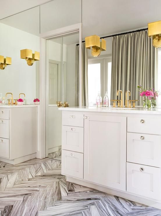 """A set of light gray washstands make up 'his and her"""" bathroom vanity area, symmetrically designed with full wall mirrors, brass octagonal wall sconces and glass cabinet hardware accents."""