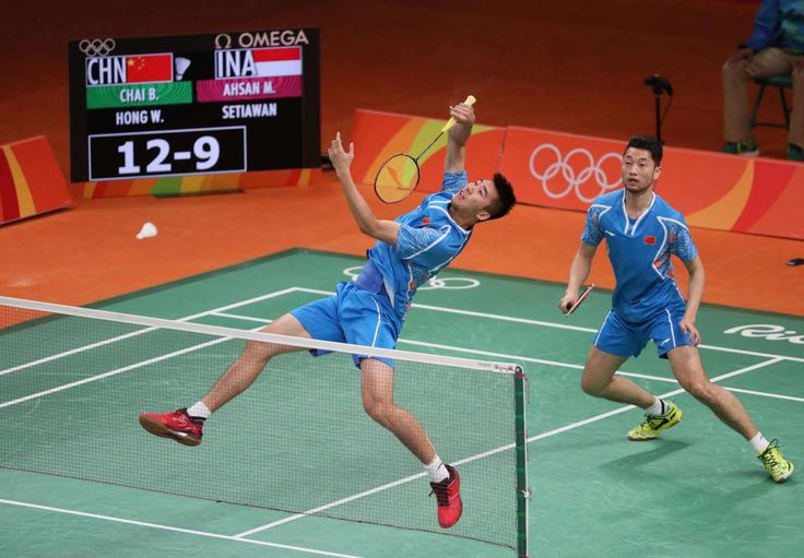 Biao Chai and Wei Hong (CHN) in action against Mohammad Ahsan and Hendra Setiawan (INA) during men's singles group stage badminton play.